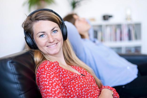 Adolescente escuchando música con auriculares y mirándote sentado en un sofá