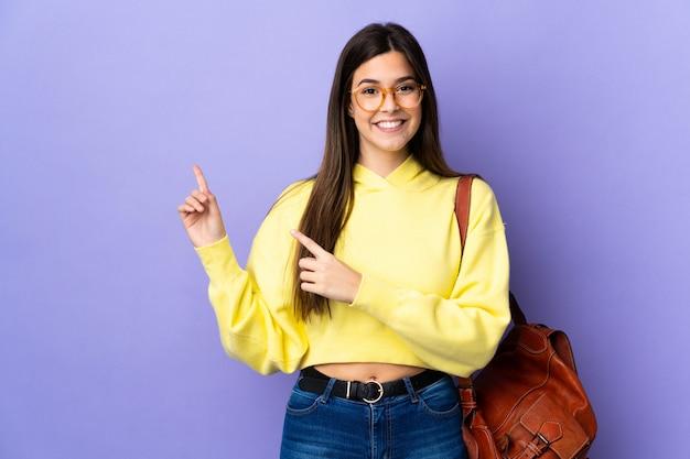 Adolescente estudiante brasileña chica aislada pared púrpura dedo señalador hacia un lado