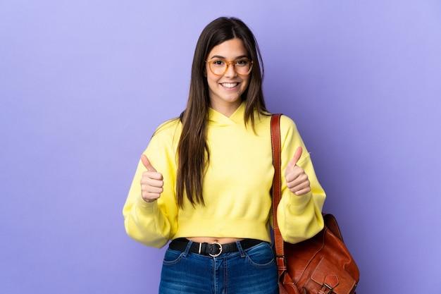 Adolescente estudiante brasileña sobre pared púrpura aislado dando un gesto de pulgares arriba