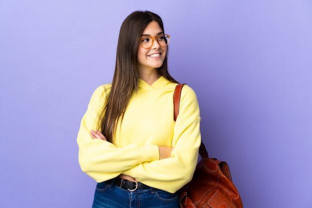 Adolescente estudiante brasileña sobre pared púrpura aislado mirando hacia el lado