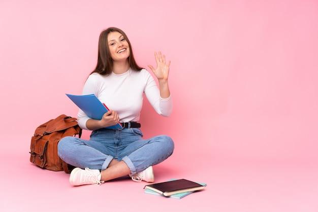 Adolescente estudiante caucásico niña sentada en el piso aislado en rosa saludando con la mano con expresión feliz