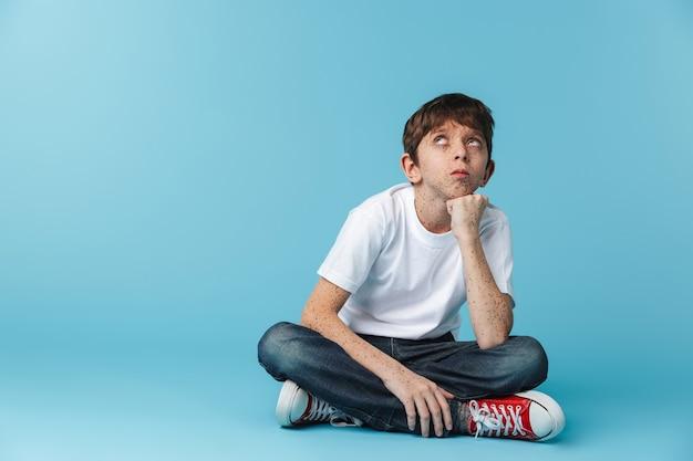 De adolescente europeo con pecas vistiendo camiseta blanca casual mirando hacia arriba mientras está sentado en el piso aislado sobre la pared azul