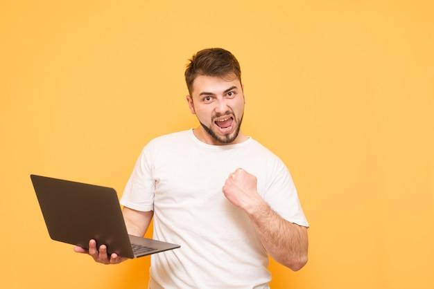 Adolescente feliz con barba de pie en amarillo con un portátil en sus manos