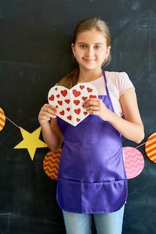 Adolescente feliz con corazón de papel