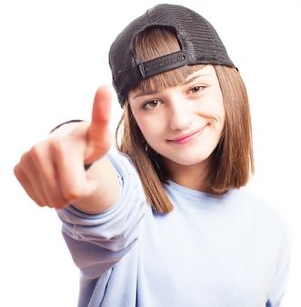 Adolescente feliz con una gorra y mostrando un gesto con la mano
