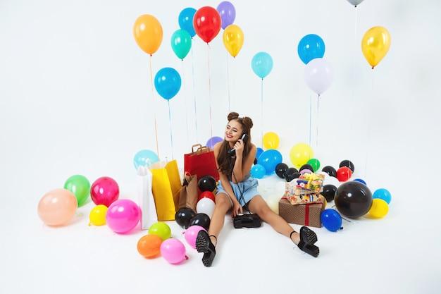 Adolescente feliz que gran fiesta de cumpleaños recibe llamadas telefónicas de la familia