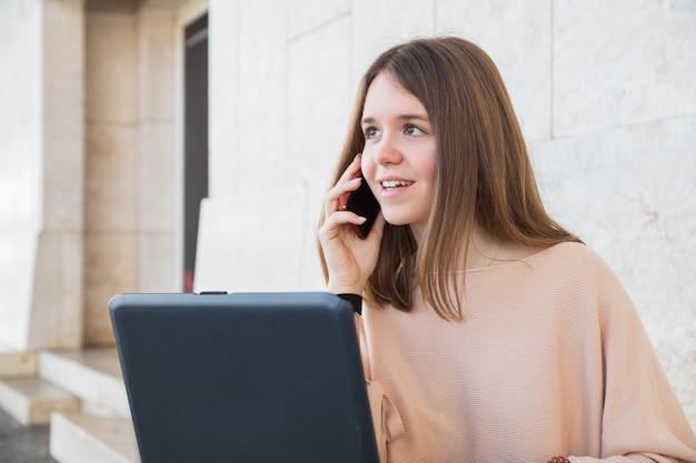 Adolescente femenino positivo que usa el ordenador portátil y el teléfono en la pared del edificio