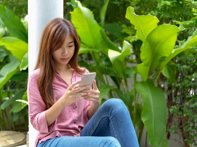 Adolescente femenino relajado sentado contra el poste y utilizando teléfonos inteligentes en el jardín