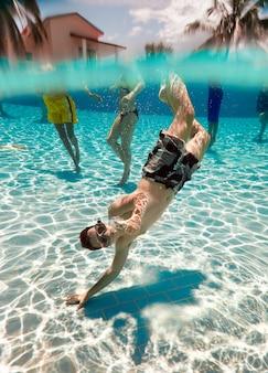Adolescente flota bajo el agua en la piscina