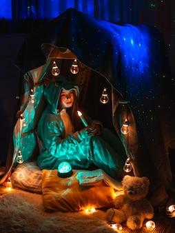 Adolescente en forma de anime sentado en la tienda de juego en casa. paisaje con fantástica iluminación de guirnaldas.