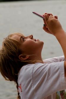 Adolescente, fotografiando con un teléfono móvil, lago de los bosques, ontario, canadá