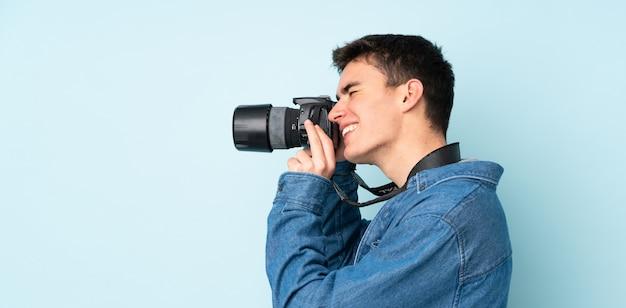 Adolescente fotógrafo hombre aislado sobre fondo azul.