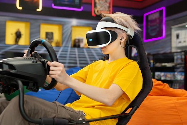 Adolescente con gafas de realidad virtual, que se aferra al volante y juega un juego de computadora en la consola