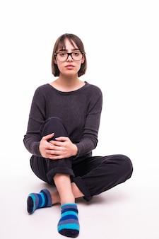 Adolescente con gafas sentado en el suelo aislado