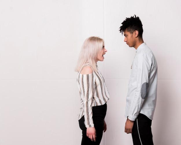 Adolescente gritando a su novio mirándolo seriamente contra el piso blanco