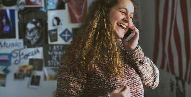 Adolescente hablando por un teléfono en un dormitorio