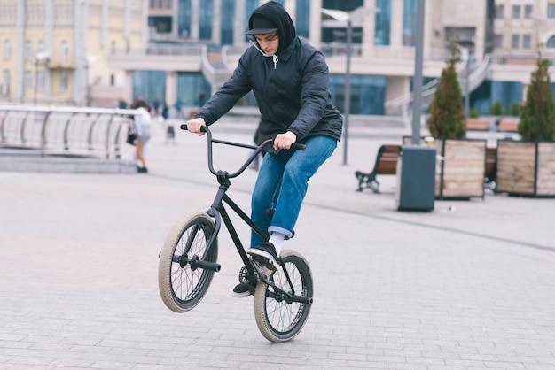 El adolescente hace trucos en el bmx. el ciclista de bmx monta una bicicleta por el parque y hace trucos. concepto bmx
