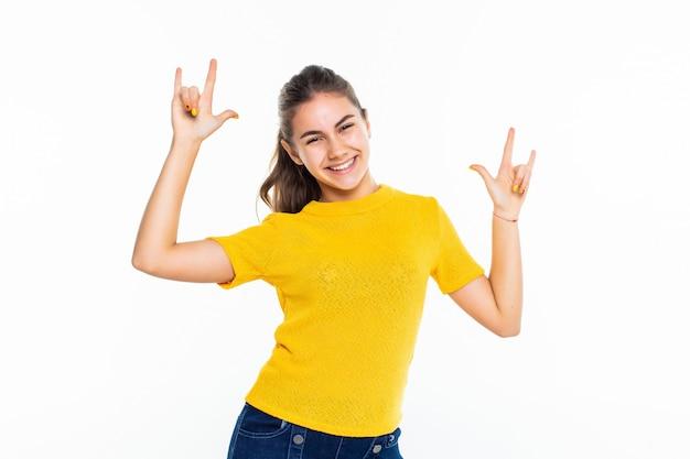 Adolescente haciendo rock gesto sobre pared blanca