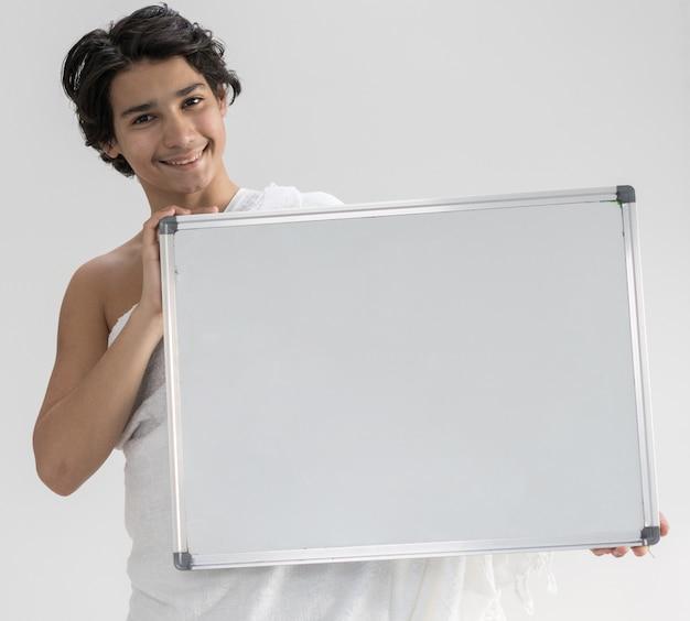 Adolescente con ihram para hajj sosteniendo un tablero de espacio de copia