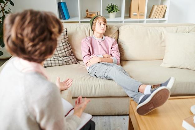 Adolescente indiferente ignorando la pregunta del psicólogo