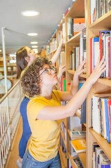 Adolescente inteligente buscando libro cerca de un amigo