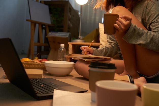 Adolescente irreconocible sentado en la computadora portátil tomando notas y bebiendo té
