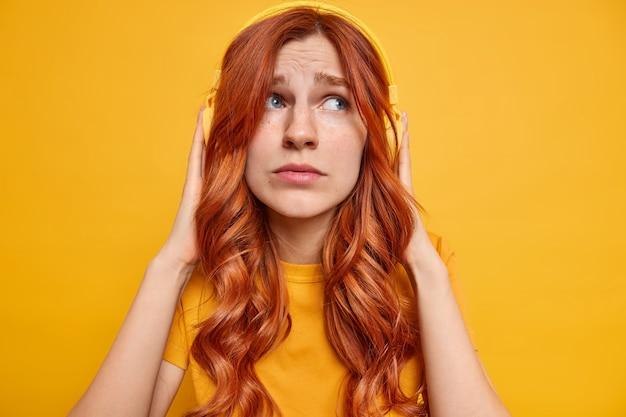 La adolescente jengibre melancólica disgustada mantiene las manos en los auriculares estéreo piensa en algo triste mientras escucha música vestida informalmente mira a un lado con tristeza