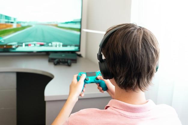 Adolescente juega un juego de computadora con auriculares y un joystick, consola de juegos.