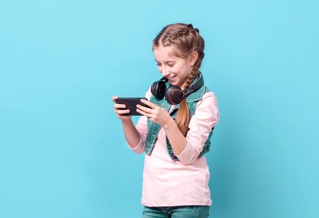 Adolescente jugando con smartphone sobre fondo azul.