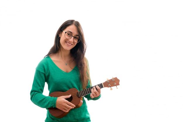Adolescente jugando un ukelele aislado sobre fondo blanco.