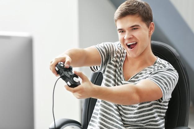 Adolescente jugando videojuegos en casa