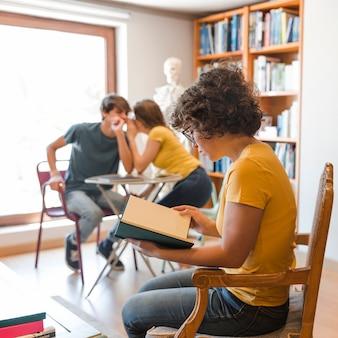 Adolescente leyendo cerca de compañeros de clase chismes