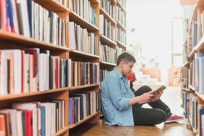 Adolescente leyendo entre estantes