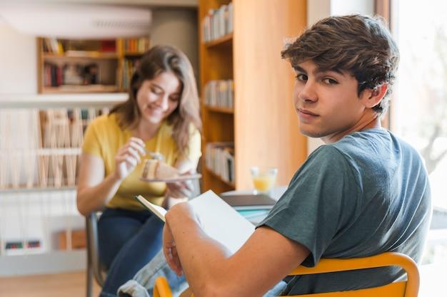 Adolescente con libro sentado cerca de la novia