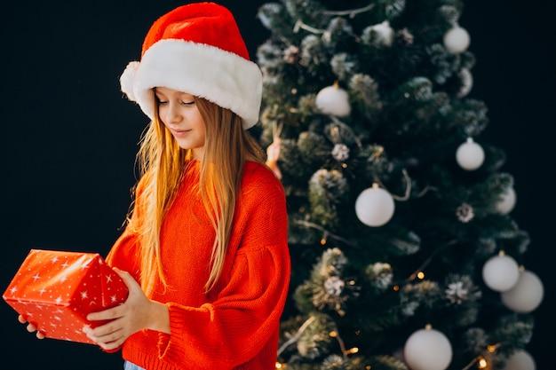 Adolescente linda chica con sombrero rojo de santa por árbol de navidad