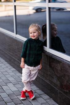 Adolescente lindo que lleva la ropa de moda del inconformista que presenta sobre la pared de ladrillo blanca