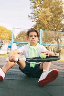 Adolescente lindo sentado en la cancha de tenis y descansando después de un entrenamiento. deporte, deportista, estilo de vida