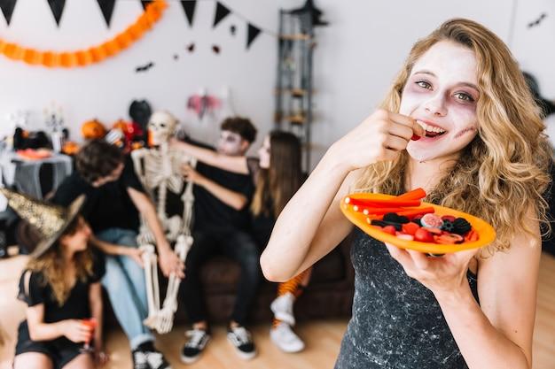 Adolescente con maquillaje de zombie y plato naranja comiendo mermelada
