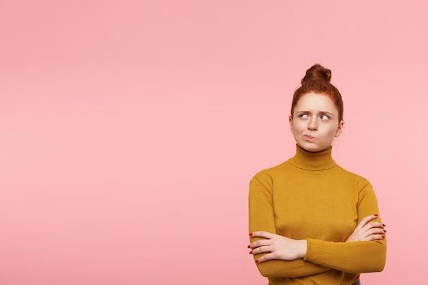 Adolescente, maravilla busca mujer pelirroja con pecas y moño. lleva un suéter de cuello alto dorado y tiene los brazos cruzados. mirando a la izquierda en el espacio de la copia sobre la pared rosa pastel