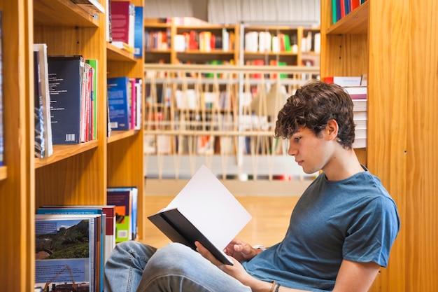 Adolescente masculino apoyado en la estantería y la lectura