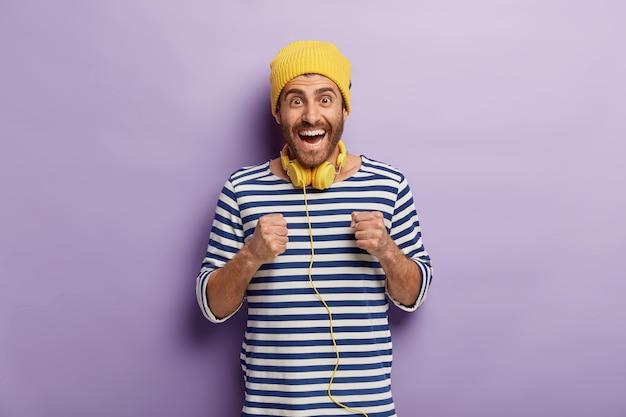 Adolescente masculino feliz aprieta los puños, anticipa algo con imaptiene