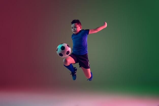 Adolescente masculino de fútbol o jugador de fútbol, niño sobre fondo degradado en luz de neón - movimiento, acción, concepto de actividad