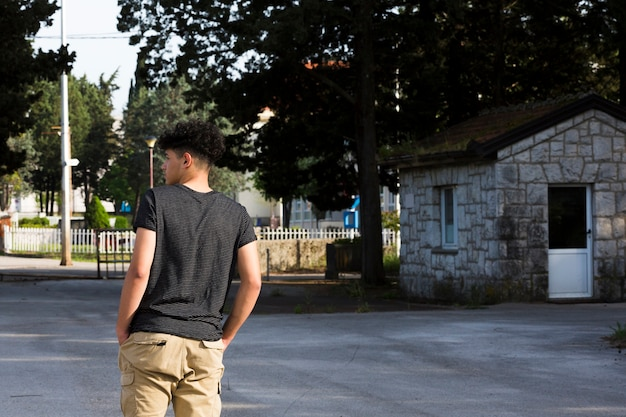 Adolescente masculino de pie y soñando despierto en la calle
