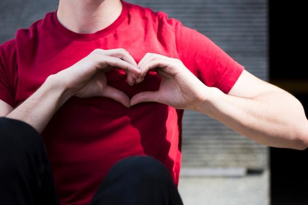 Adolescente masculino que muestra forma del corazón con las manos