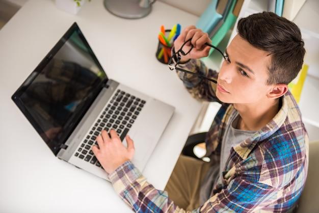Adolescente masculino sentado en la mesa en casa y usando la computadora portátil.