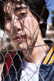 Adolescente mirando a través de la cerca en la calle