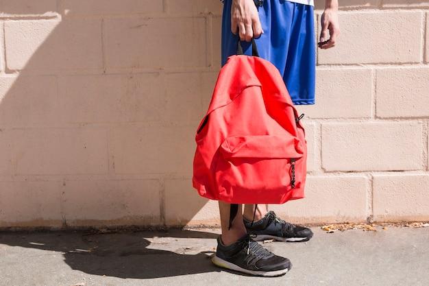 Adolescente con mochila roja en calle.