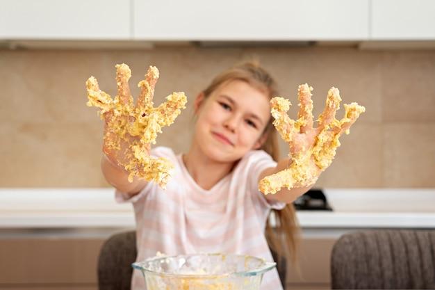 Adolescente muestra las manos sucias en masa divirtiéndose en la cocina