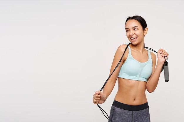 Adolescente, mujer asiática de aspecto deportivo con cabello largo oscuro. vistiendo ropa deportiva y sosteniendo una cuerda para saltar sobre su cuello. mirando coqueto a la izquierda en el espacio de la copia, aislado sobre fondo blanco.