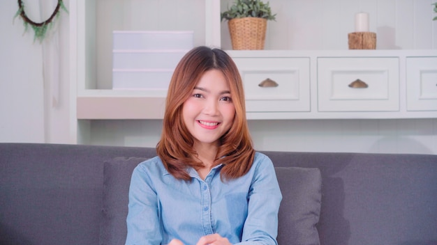 Adolescente mujer asiática sintiendo feliz sonriendo y mirando a la cámara mientras se relaja en su sala de estar